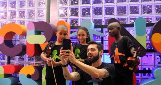 Crianças da Orquestrando a Vida posam com o jornalista Cauê Fabiano
