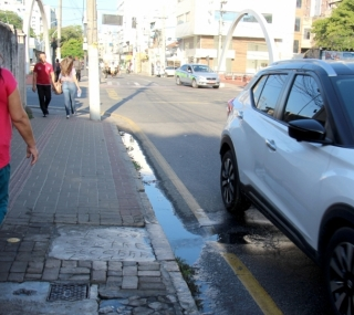 Carros passam em buraco e jogam água suja