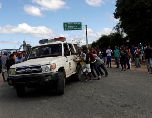 Ambulância que transportava pessoas feridas durante confrontos no sul da cidade venezuelana de Kumarakapay, perto da fronteira com o Brasil, é assistida por pessoas na fronteira entre a Venezuela e o Brasil, em Pacaraima.