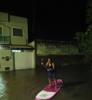 Moradora usa prancha de stand up paddle na rua