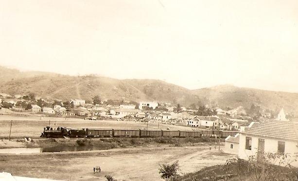 Trem da RFFSA passando por dentro da cidade, formada ao redor da linha