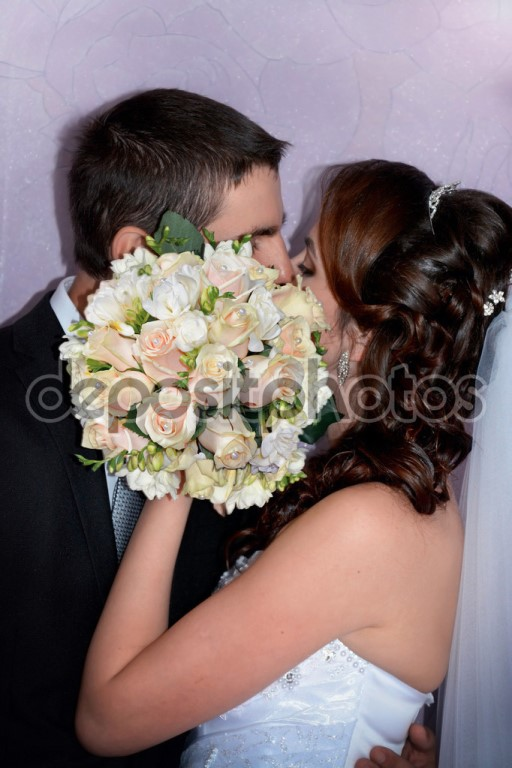 Married couple. Bride and groom kissing behind wedding bouquet