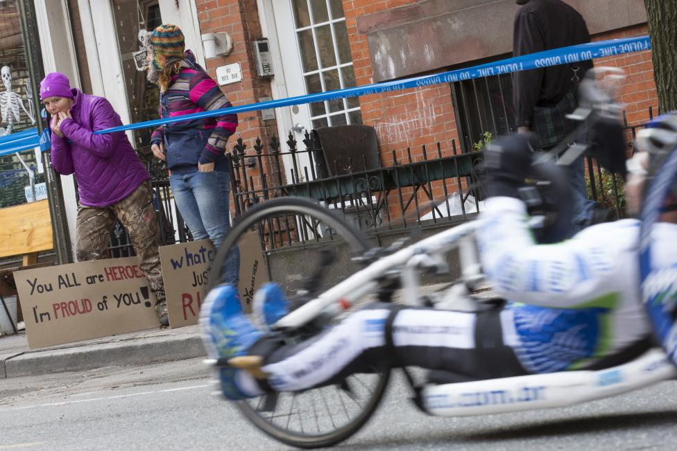 Spectators cheer as wheelchair racer passes during the 2014 New York City Marathon in the Brooklyn Borough of New York