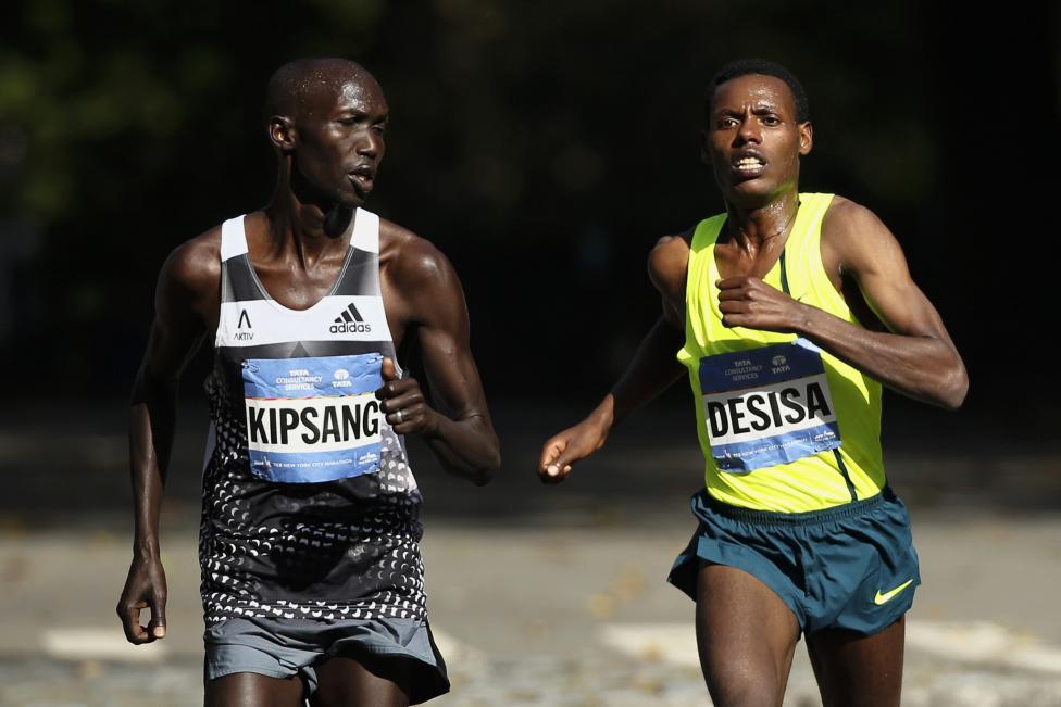 Wilson Kipsang of Kenya looks at competitor Lelisa Desisa of Ethiopia, as he leads men's elite pack during New York City Marathon in New York
