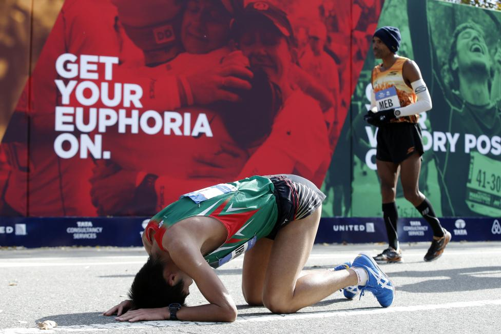 Kawauchi of Japan drops to his knees after finishing the 2014 New York City Marathon in Central Park in Manhattan