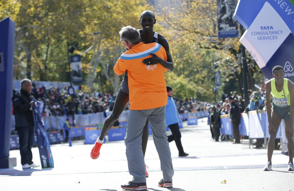 Supporter lifts Kipsang of Kenya off the ground after he crossed the finish line to win the men's professional division of the 2014 New York City Marathon in Central Park in Manhattan